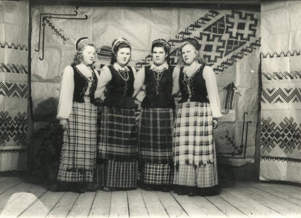Tremtinės saviveiklininkės juostų raštais puoštoje scenoje. Dėvi pačių pasisiūtus tautinius drabužius, prijuostėms panaudotos motinų skarelės. Chara Kutulas Zaigrajevo rajone Buriatijoje, ~1957 m. Iš dešinės antra G. Radėnienė.